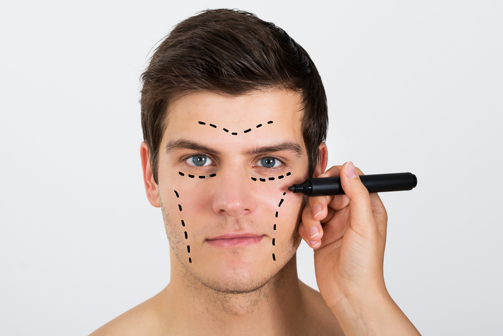 Woman Drawing dots on Young Man's Face